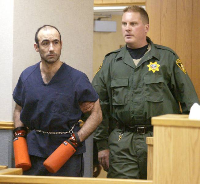 A Las Vegas Metro Police S.E.R.T officer escorts Jose Vigoa into Las Vegas Justice Court on June 6, 2002.