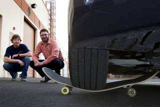 Ross Graham, left, and Clinton Anderson pose as a car rests on one of their skateboards at the Colonial Brand skateboard company manufacturing facility in Las Vegas Thursday, Jan. 26, 2012. The start-up company is planning to market their hand-made skateboards as the world's strongest.