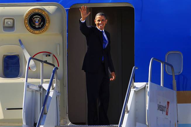 President Obama waves to the media before boarding Air Force One at McCarran International Airport after a visit to Las Vegas Thursday, Jan. 26, 2012.
