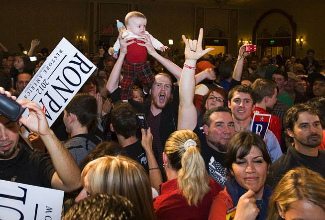 A man holds up a baby as Republican presidential candidate Rep. Ron Paul, R-Texas, leaves the stage after speaking at a rally at the Green Valley Ranch Resort in Henderson on Tuesday, Jan. 31, 2012.