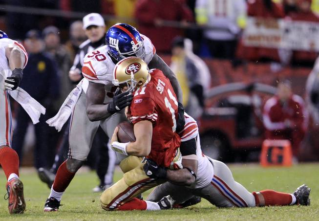 New York Giants defensive linemen Justin Tuck (91) and Jason Pierre-Paul (90) make a sack during an NFC Championship NFL football game against San Francisco 49ers quarterback Alex Smith (11) on Sunday, Jan. 22, 2012, in San Francisco. The Giants won the game, 20-17.