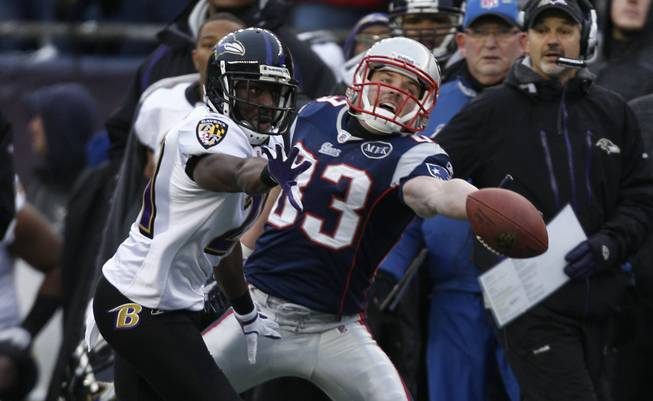 New England Patriot Wes Welker (83) stretches for the ball as Baltimore Ravens Lardarius Webb (21) runs in to block the catch during the first half of the AFC Championship NFL football game, Sunday, Jan. 22, 2012, in Foxborough, Mass.)
