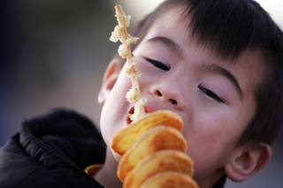 Zayde Rubianes, 6, of Las Vegas enjoys a tornado potato at the South Point Gourmet Food Truck Fest in the parking lot of the South Point in Las Vegas Wednesday, Feb. 1, 2012.