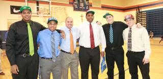 Bishop Gorman High football players, from left, Ronnie Stanley (Notre Dame), Shaquille Powell (Duke), coach Tony Sanchez, Ron Scoggins Jr. (UNLV), Zach Hutchins (Montana State) and Marc Philippi (UNLV) pose for a photo on national signing day.