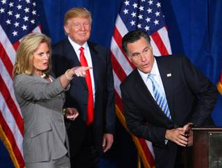 Ann Romney points out someone in the audience to her husband Republican presidential candidate, former Massachusetts Gov. Mitt Romney, after businessman Donald Trump, center, endorsed Romney's presidential bid during a news conference at the Trump International Hotel  in Las Vegas, Nevada February 2, 2012.