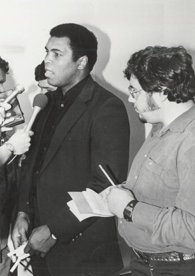 Muhammad Ali talks to reporters after surrendering his Nevada boxing license on Dec. 29, 1980, during a Nevada Athletic Commission hearing in Las Vegas. Ed Koch, former Las Vegas Sun reporter, is standing beside Ali, taking notes.