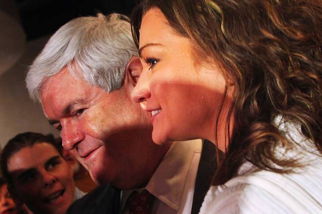 Republican presidential candidate Newt Gingrich has his photo taken with a woman who had just identified herself as being with the Occupy movement after speaking at a town hall-style meeting with business and community leaders from the Las Vegas Latino community Thursday, Feb. 2, 2012.