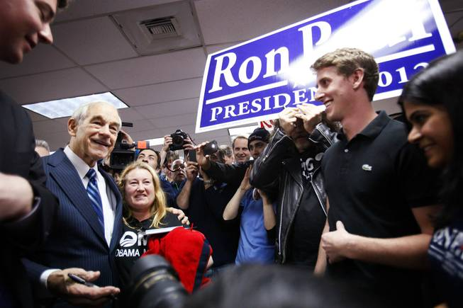 Rep. Ron Paul poses for photos while campaigning at American Shooters, an indoor gun range and retail store in Las Vegas Friday, Feb. 3, 2012.