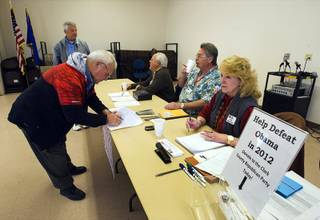 Roy L. Phillips, left, of Cal-Nev-Ari, signs-in for a Republican caucus at a community center in Searchlight Saturday, February 4, 2012.