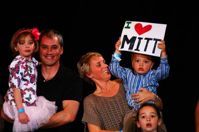 "In the arms of his mom, Tommy Sholeff holds an ""I love Mitt"" sign in support of Republican presidential candidate Mitt Romney while attending the Nevada Republican caucus Saturday, Feb. 4, 2012, at the Red Rock Hotel and Casino in Las Vegas.  From left, Emily, Jim, Amy, Tommy and Katie Sholeff."