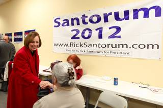 Sharron Angle shake hands with a Rick Santorum supporter at Santorum's campaign headquarters in Las Vegas Friday night. Angle endorsed Santorum on Wednesday.