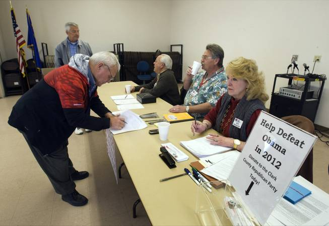 Roy L. Phillips, left, of Cal-Nev-Ari signs in for a Republican caucus at a community center in Searchlight, Nev., about 60 miles southeast of Las Vegas on Saturday, Feb. 4, 2012.