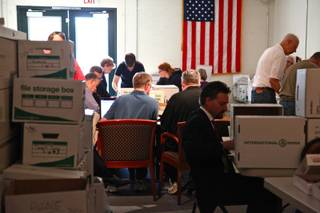 Volunteers count and record caucus totals at Clark County GOP headquarters Sunday morning.