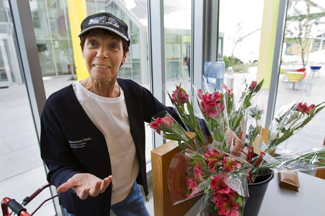 Volunteer Lydia Woltag, 66, stands by flowers at the Cleveland Clinic Lou Ruvo Center for Brain Health Tuesday, February 7, 2012. In addition to helping brighten their day, the flowers help remind patients with Alzheimer's disease of the center. Patients remember that the center is the place where they get a flower, a volunteer said.