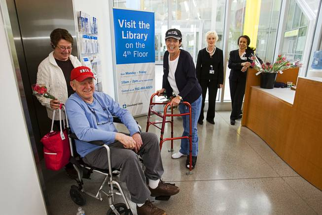 Patient Jerry Wilson and his wife Mamie prepare to leave the Cleveland Clinic Lou Ruvo Center for Brain Health after getting a flower  from volunteer Lydia Woltag, center, Tuesday, February 7, 2012. In addition to helping brighten their day, the flowers help remind patients with Alzheimer's disease of the center. Patients remember that the center is the place where they get a flower, a volunteer said.  In the background are volunteers Volunteers Jan Shaw, left, and Barbara Brisco.