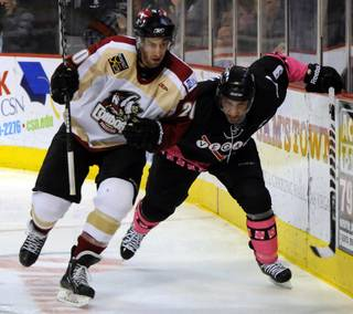 Defensemen Alain Goulet, left and Mike Madill battle for position along the boards behind the Condors net as Las Vegas hosted Bakersfield on Friday night at the Orleans Arena.