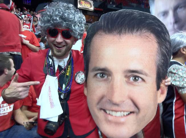 UNLV student Joey Shea holds up a giant cutout of Dave Kirvin's head, because an important college basketball game calls for such.