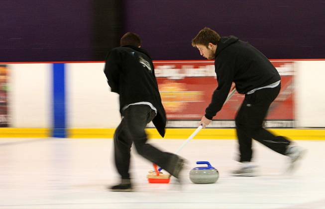 Kyle Volin, left and Zachary Clayton sweep in front of a stone during an open practice session of the Las Vegas Curling Club at the Las Vegas Ice Center on West Flamingo Road Sunday, Feb 12, 2012. Sweeping allows the stone to travel farther and gives a degree of directional control.