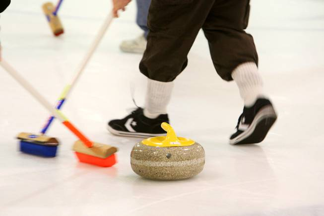 Curling students sweep in front of a stone during a practice session of the Las Vegas Curling Club at the Las Vegas Ice Center on West Flamingo Road on Feb 12, 2012. Sweeping allows the stone to travel farther and gives a degree of directional control.