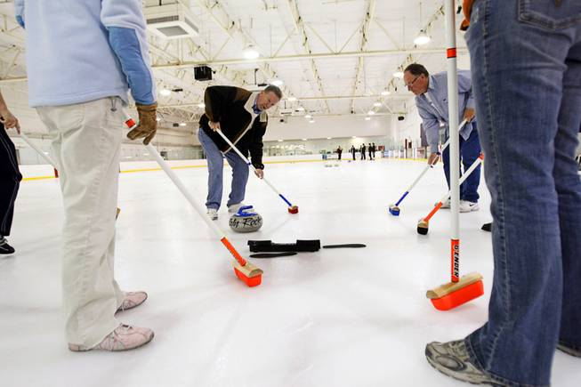 Curling instructor Gary Hunneyman, left, gives lessons on sweeping during a practice session of the Las Vegas Curling Club at the Las Vegas Ice Center on West Flamingo Roadon Feb 12, 2012. Dave Greenman is at right.