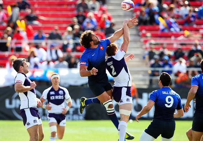 France's Jean Bapiste Mazoue, left, and Scotland's Michael Fedo jump for the ball during the USA Sevens Rugby tournament at Sam Boyd Stadium on Sunday, Feb. 12, 2012. France beat Scotland 22-7 to win the Shield Final.