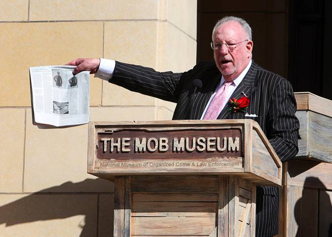 Former Las Vegas Mayor Oscar Goodman holds up a news article with a story on The Mob Museum during the museum's grand opening in downtown Las Vegas, Tuesday February 14, 2012. Goodman is also known as a former mob attorney for representing alleged mobsters such as Meyer Lansky, Frank Rosenthal and Anthony Spilotro.