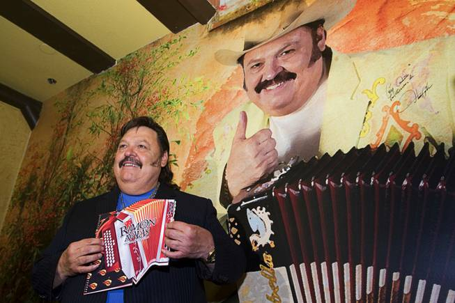 "Ramon Ayala holds an accordion-shaped menu as he poses by a image of himself during the grand opening of Ramon Ayalas Cocina & Cantina at Buffalo Bills Resort in Primm Thursday, Feb. 16, 2012. Known as the ""King of the Accordion,"" Ayala is a Mexican-American musician that has recorded more than 105 albums and received four Grammy and Latin Grammy Awards."