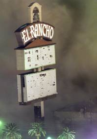 A cloud of dust billows around the El Rancho sign after the hotel-casino was imploded early Tuesday, Oct. 3, 2000.