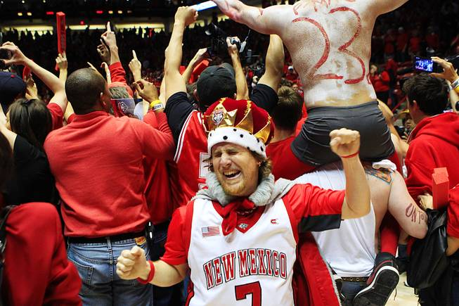 New Mexico fans storm the court after defeating UNLV 65-45 to take sole possession of first place in the Mountain West Saturday, Feb. 18, 2012 at The Pit in Albuquerque.