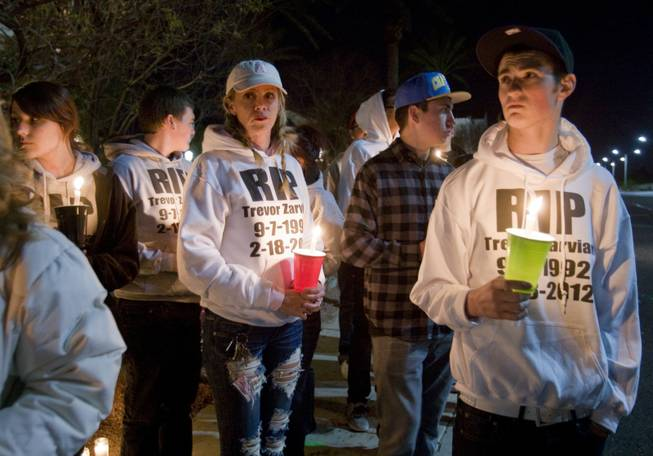 Jen Marquardt, left, and Richie Peterson wear sweatshirts in honor of Trevor Zarvian, 19, during a vigil for Zarvian and and Johnny Castiblanco, 19, at Windmill Parkway and Thayer Avenue in Henderson Sunday, Feb.19, 2012.  The pair died in an auto accident at the site Saturday. Also killed was an 86-year-old man. STEVE MARCUS