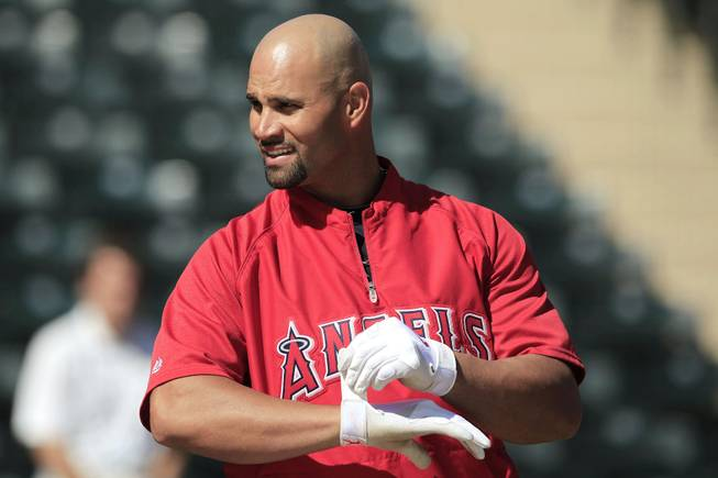Los Angeles Angels' Albert Pujols adjusts his batting gloves during spring training baseball practice Monday, Feb. 27, 2012, in Tempe, Ariz.