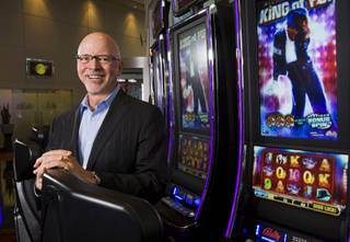 Richard Haddrill, CEO of Bally Technologies, poses by a Michael Jackson-themed slot machine Monday, March 5, 2012.