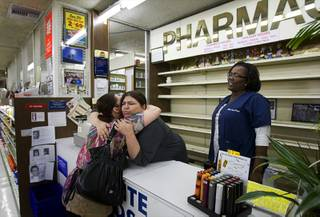 Vicki Kelesis, a waitress at Tiffany's Cafe, gives a hug to pharmacy technician Mandy Tucker, as co-worker Sharron Manzy looks on during the last day of operation at the White Cross Pharmacy on Las Vegas Boulevard South Tuesday, March 6, 2012. The pharmacy, the first 24-hour pharmacy in Las Vegas, opened in 1955 but closed at 7 p.m. Tuesday night.