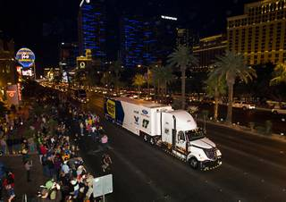 Matt Kenseth's car hauler passes fans in front of Bally's during a NASCAR hauler parade on Las Vegas Boulevard Thursday, March 8, 2012.