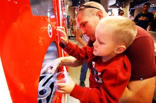 Brad Stewart helps his son Steven Stewart, 5, both of Salt Lake City, Utah, pour some root beer using the Coca-Cola Freestyle machine at the World of Coca-Cola on The Strip in Las Vegas on Friday, March 9, 2012.