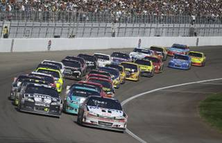 Tony Stewart (14) leads coming out of a restart during the NASCAR Sprint Cup Series auto race, Sunday, March 11, 2012, in Las Vegas.