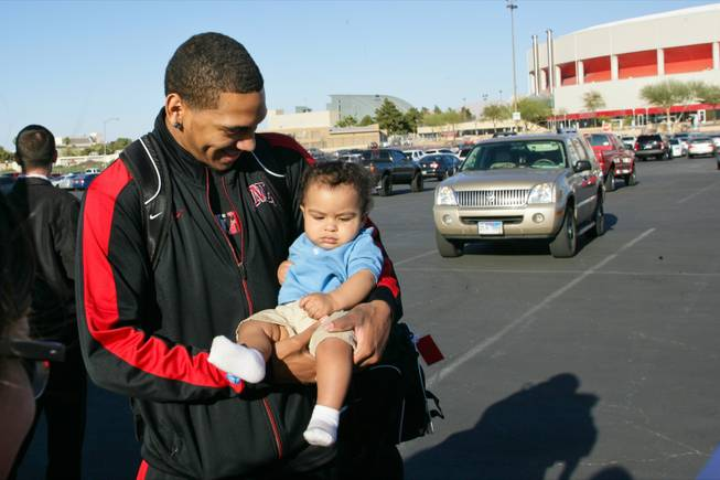 UNLV's Anthony Marshall takes a photo with a young Rebel fan before boarding a bus to Albuquerque for the NCAA Tournament, Tuesday March, 13 2012.
