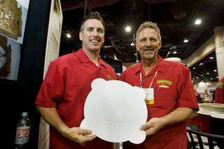 Jeff Pugh, left, Perfect Crust CEO, and Tom Esterley, vice president of sales and marketing, pose with the Perfect Crust Pizza Liner during the International Pizza Expo at the Las Vegas Convention Center Wednesday, March 14, 2012. The special paper liner absorbs excess oil and is embossed to keep the crust slightly elevated over the paper, keeping the crust crisp in the delivery box.