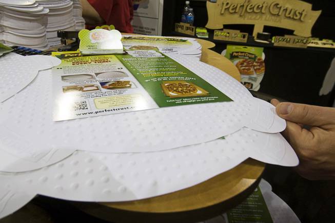 The Perfect Crust Pizza Liner is displayed during the International Pizza Expo at the Las Vegas Convention Center Wednesday, March 14, 2012. The special paper liner absorbs excess oil and is embossed to keep the crust slightly elevated over the paper, keeping the crust crisp in the delivery box.