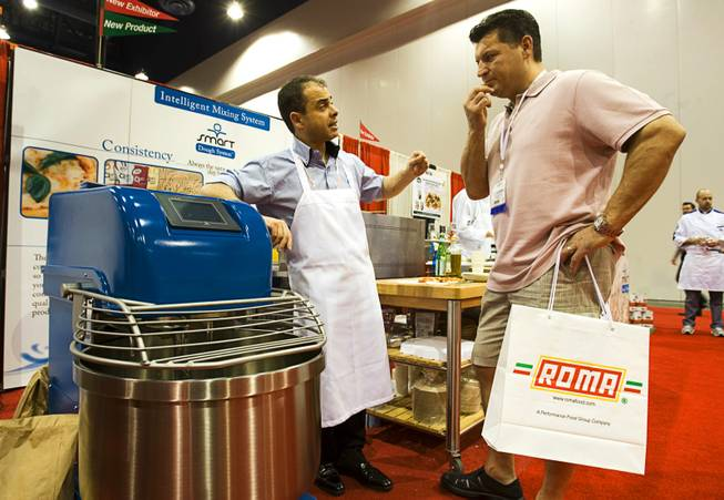 Inventor Roberto Brisciani, left, of Thinking Foods explains the features of the Smart Dough System machine to restaurant owner Celestino Gencarelli during the International Pizza Expo at the Las Vegas Convention Center Wednesday, March 14, 2012.