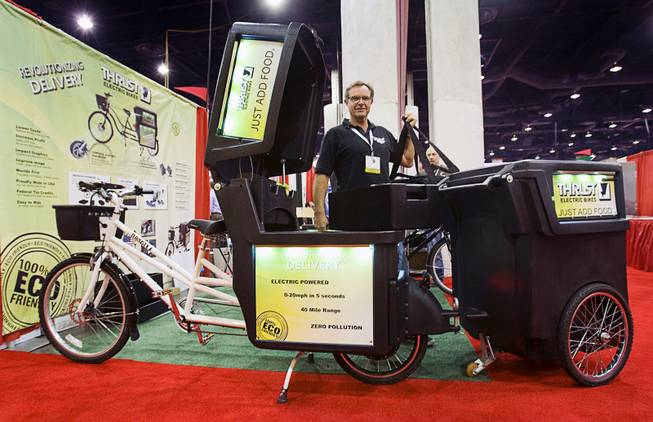 Tom Casey, president of Thrust Electric Bikes, stands behind a pizza delivery bike during the International Pizza Expo at the Las Vegas Convention Center Wednesday, March 14, 2012. The bike comes equipped with a delivery container and graphics and LED lighting. An optional trailer can be used for more delivery storage or as a food vending station.