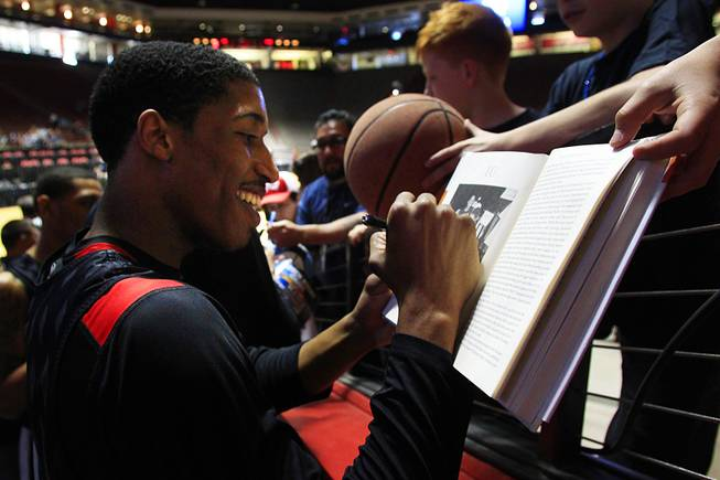 "Justin Hawkins signs a copy of the book ""Play Their Hearts Out,"" in which he is featured, after practice before their second round NCAA Men's Basketball Championship game Wednesday, March 14, 2012 at The Pit in Albuquerque."