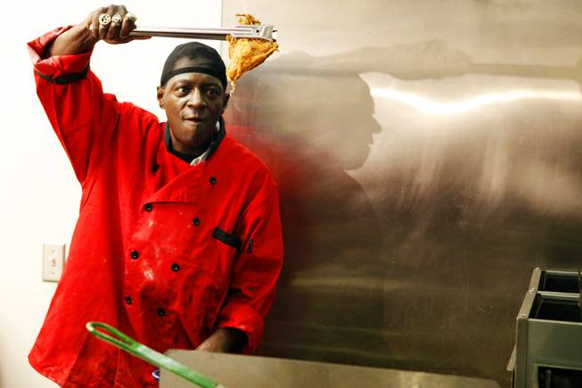 Flavor Flav prepares chicken during the grand opening of Flavor Flav's House of Flavor in Las Vegas on Thursday, March 15, 2012.