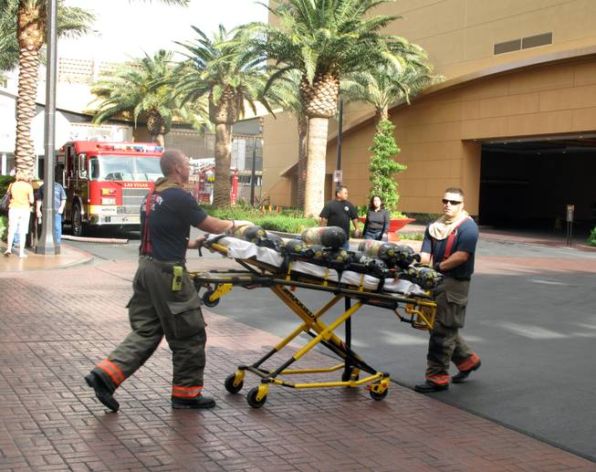 Las Vegas firefighters roll equipment toward the Golden Nugget on Thursday morning. An unidentified man was in critical condition after a fire in a room on the 22nd floor of the Rush Tower.