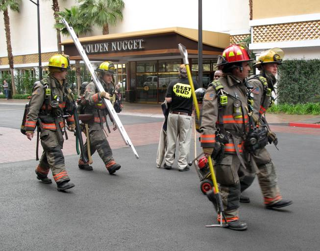 Las Vegas firefighters prepare to leave the scene of a fire Thursday morning at the Golden Nugget. A fire in the room on the 22nd floor of the Rush Tower sent an unidentified man to the hospital in critical condition.