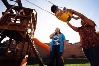 Vinil Narayan, 2, who is autistic, plays on the swing while learning communication with his mother Shika Narayan during a session with Jennifer Murdock, a developmental specialist with Easter Seals Nevada, outside his home in Henderson on Friday, March 16, 2012.