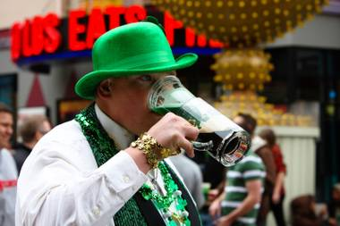 Lance Fitzgerald, of Colorado, sips a green beer stuck in his beer mug while celebrating St. Patrick's Day at Hennessey's Tavern Block Party Saturday, March 17, 2012, in Las Vegas.