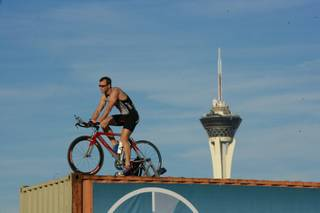 Spencer Larson rides his bicycle on top of storage containers along the I-15 during rush hour to promote exercise, Tuesday March 20, 2012.