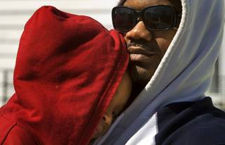 Braylyn Moffett, 4, is held by his father Antoine Moffett as he tries to stay awake for a