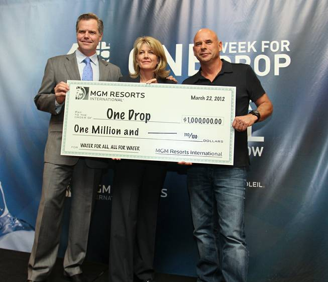 Jim Murren, Cindy Ortega and Guy Laliberte with MGM Resorts International's $1 million donation to One Drop.